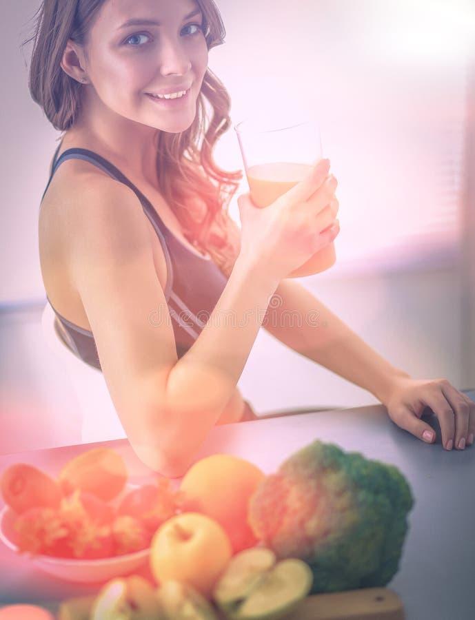 Девушка сидя в кухне на столе с плодоовощ и стеклами с соком стоковое изображение rf