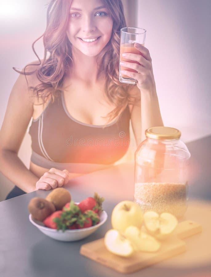 Девушка сидя в кухне на столе с плодоовощ и стеклами с соком стоковые фотографии rf