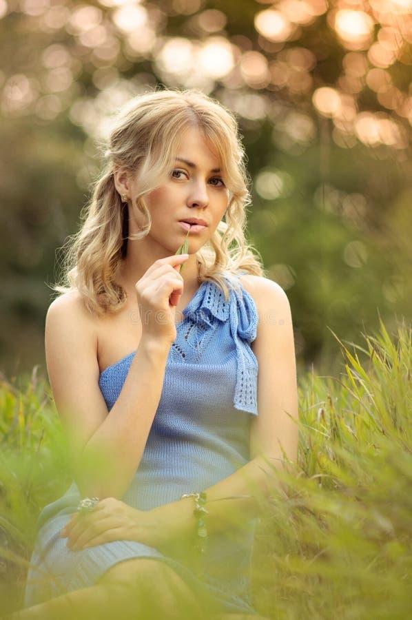 Девушка сидя в траве стоковые фотографии rf
