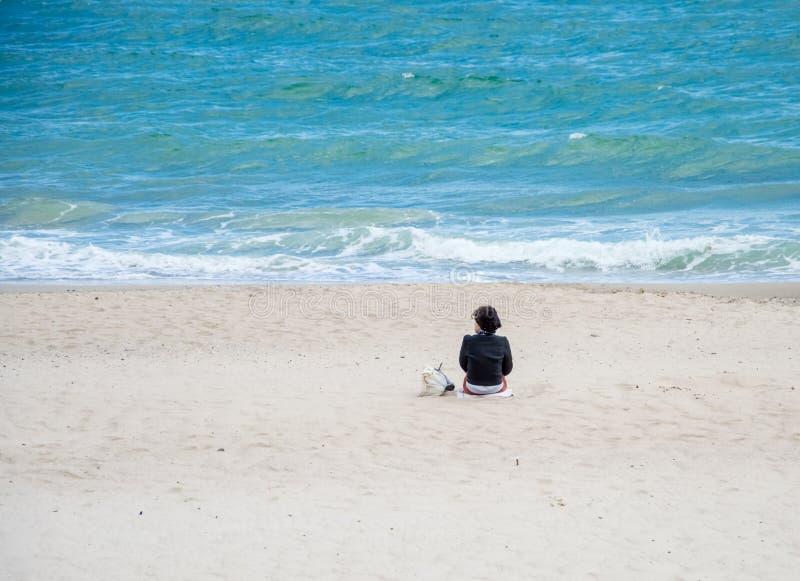 Девушка сидя на взглядах песка на море стоковое фото