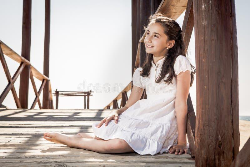 Девушка сидя на деревянном поле на пляже стоковые изображения