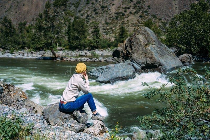 Девушка сидя на камне среди гор и смотря реку Женщина сидит около реки горы наслаждается взглядом стоковые изображения