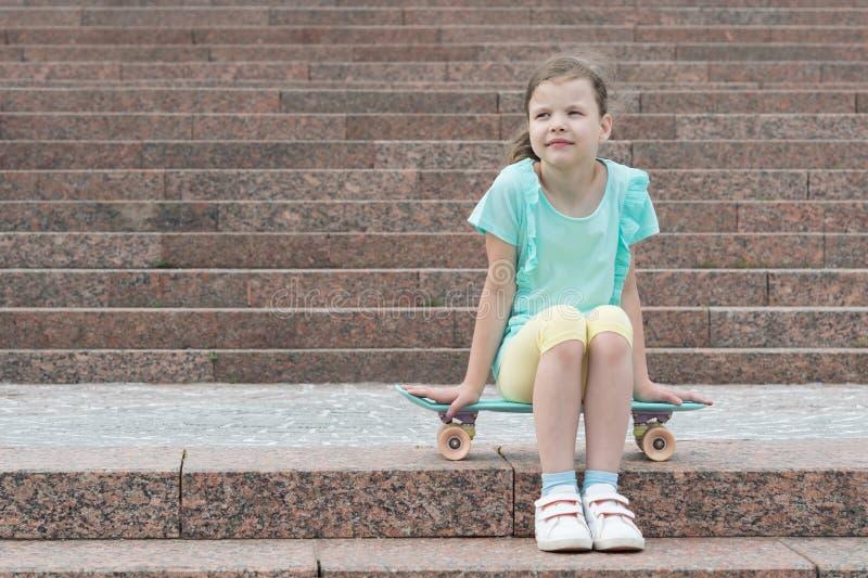 Девушка сидя на скейтборде на предпосылке лестниц стоковые изображения rf