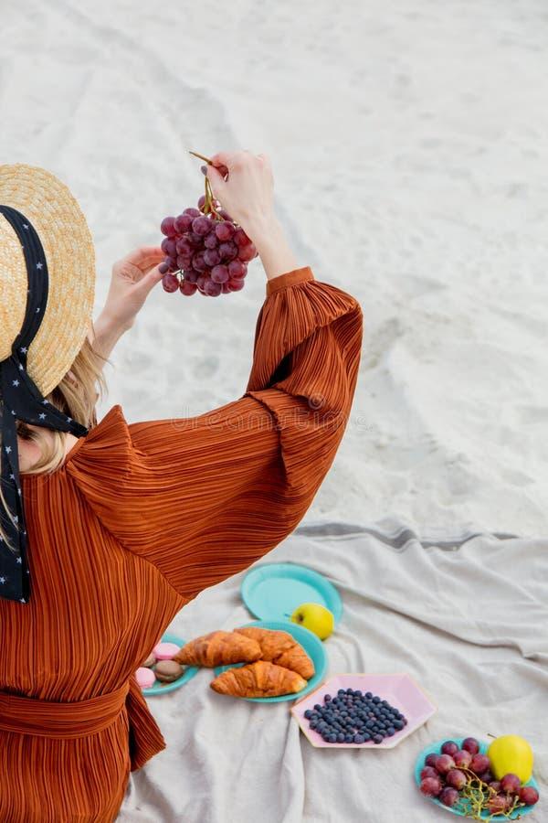 Девушка сидя на соре и держать виноградину в руке стоковые фото