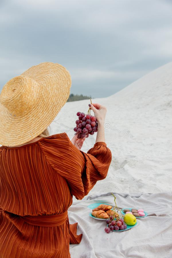 Девушка сидя на соре и держать виноградину в руке стоковые изображения
