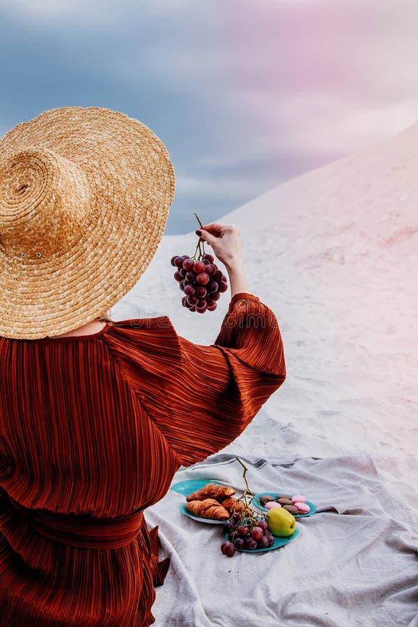 Девушка сидя на соре и держать виноградину в руке стоковое фото