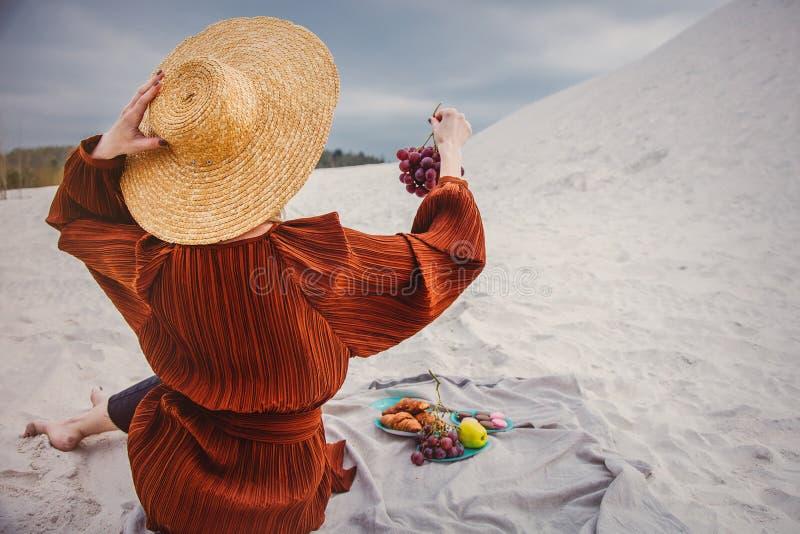 Девушка сидя на соре и держать виноградину в руке стоковые изображения rf