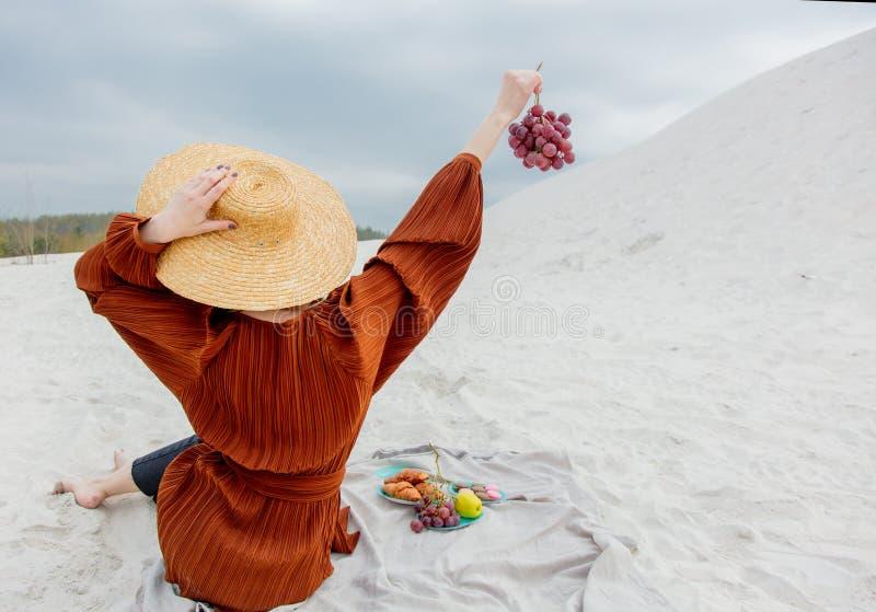 Девушка сидя на соре и держать виноградину в руке стоковое изображение