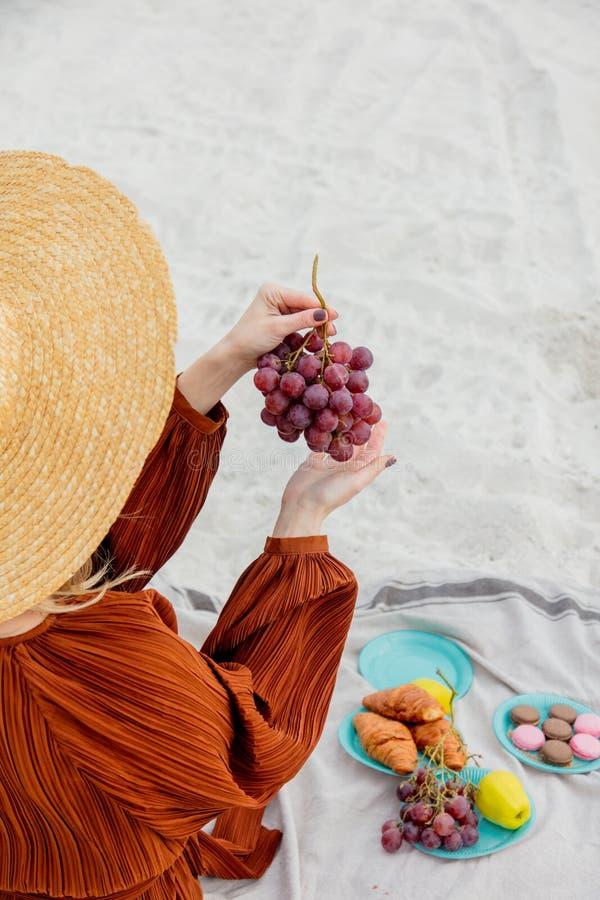 Девушка сидя на соре и держать виноградину в руке стоковая фотография rf