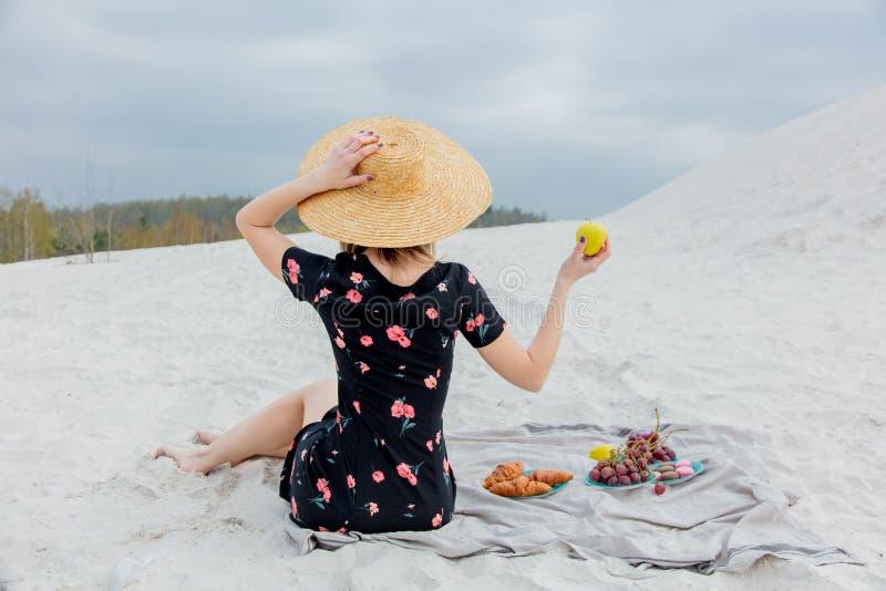 Девушка сидя на соре и держать яблоко в руке стоковые фотографии rf