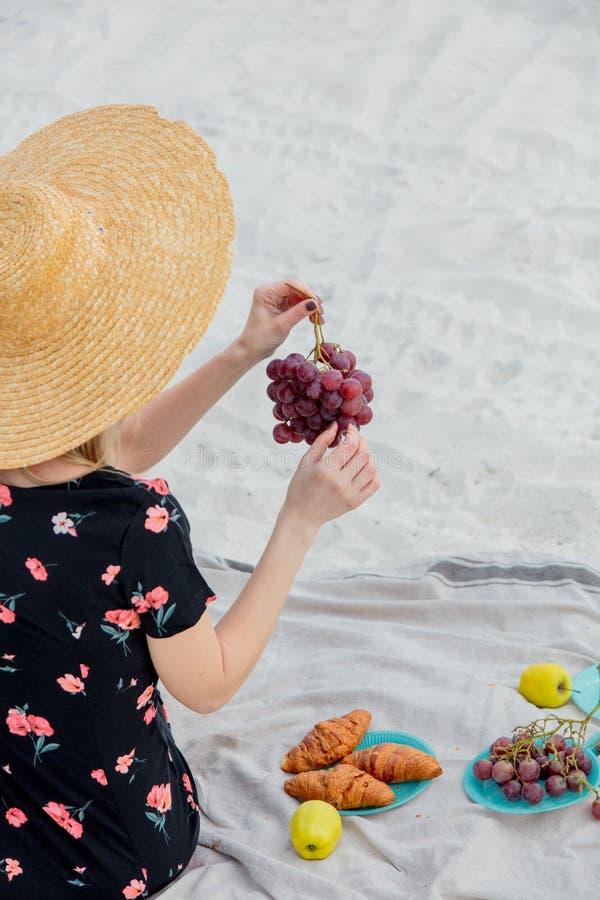 Девушка сидя на соре и держать яблоко в руке стоковое изображение