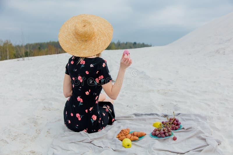 Девушка сидя на соре и держать macron в руке стоковое изображение rf