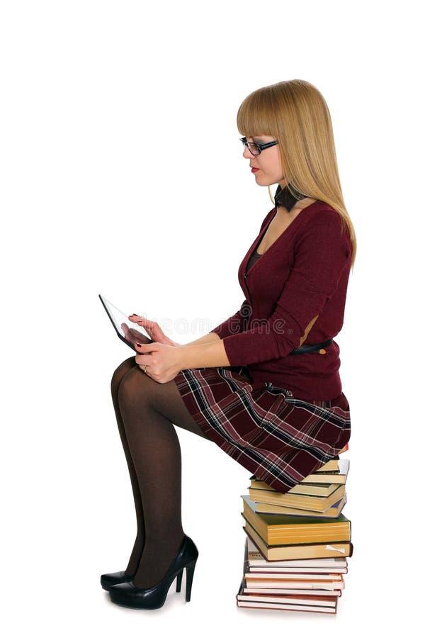 Девушка сидя на стоге книг стоковые фото