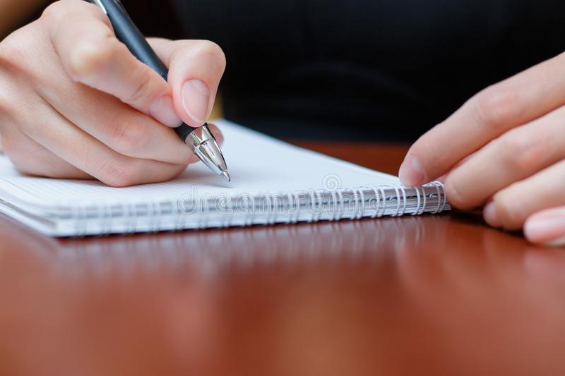 Девушка сидя на таблице с тетрадью и ручкой и пишет стоковые фотографии rf