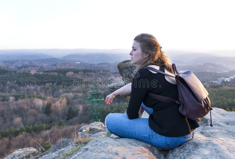 Девушка сидя на утесе над долиной горы на заходе солнца стоковые изображения