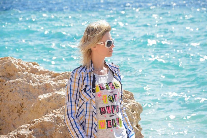 Девушка сидя около камня на пляже стоковые фото