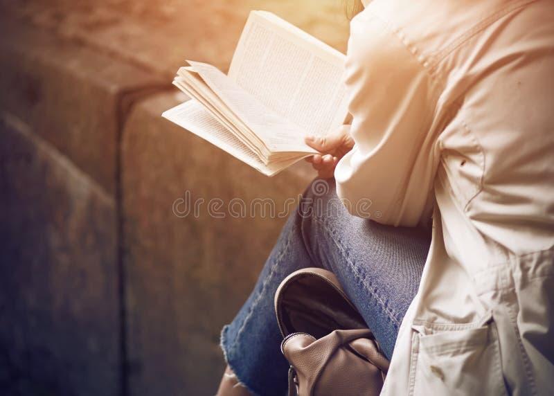 Девушка сидя читающ классическую литературу стоковые изображения rf