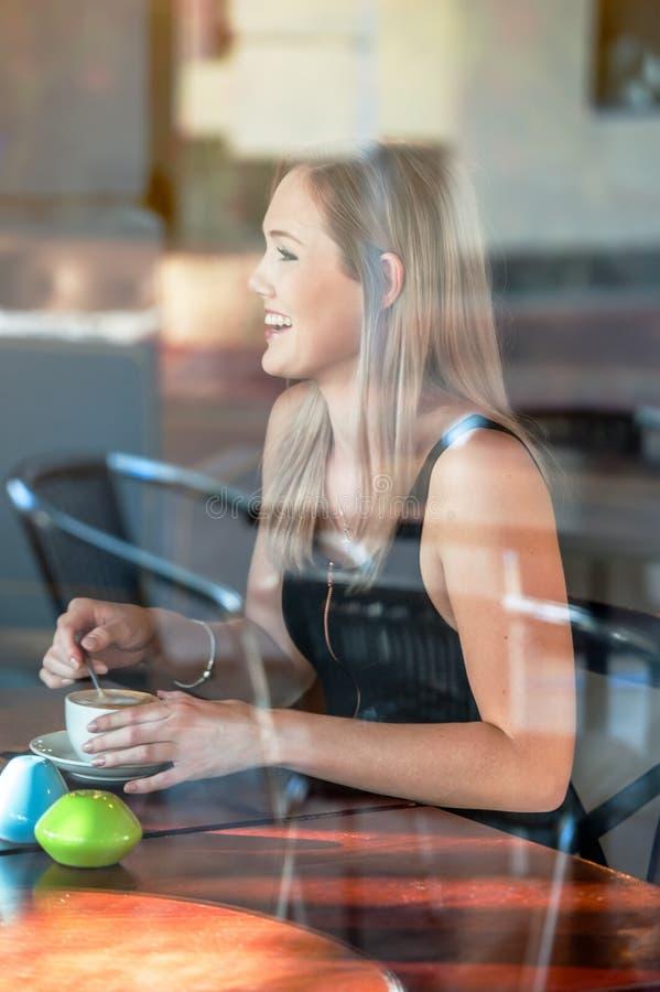 Девушка сидела в окне кофе кофейни выпивая стоковые фото