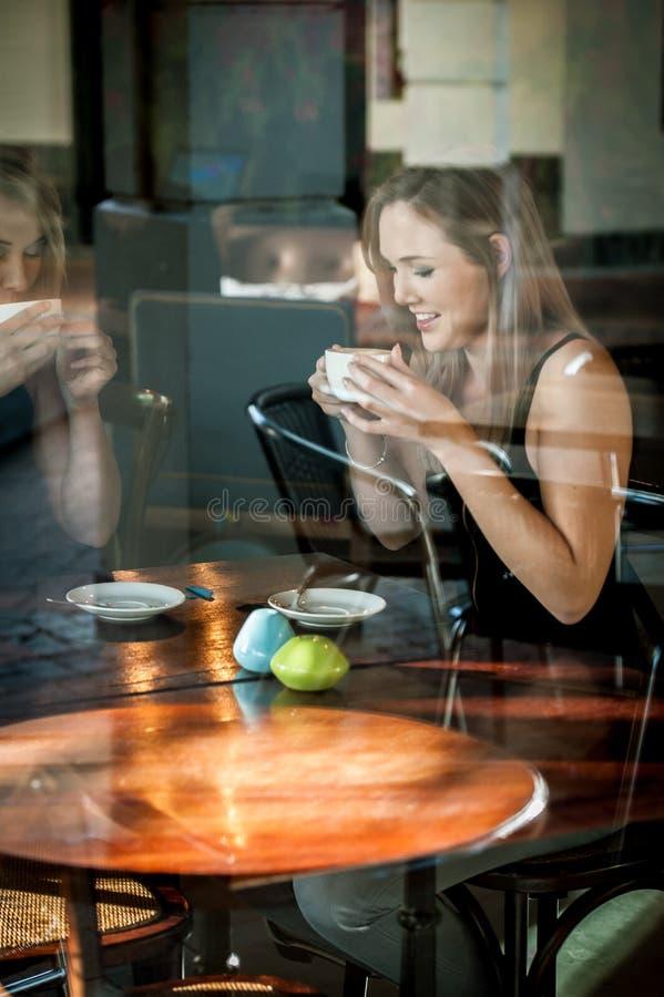 Девушка сидела в окне кофе кофейни выпивая стоковые изображения