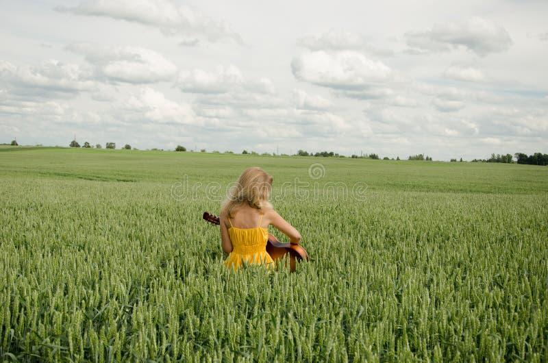 Девушка сидит в поле гитары игр рож стоковые фото