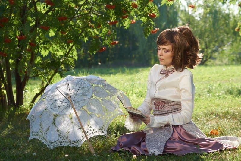 Девушка сидит и прочитала книга стоковые изображения