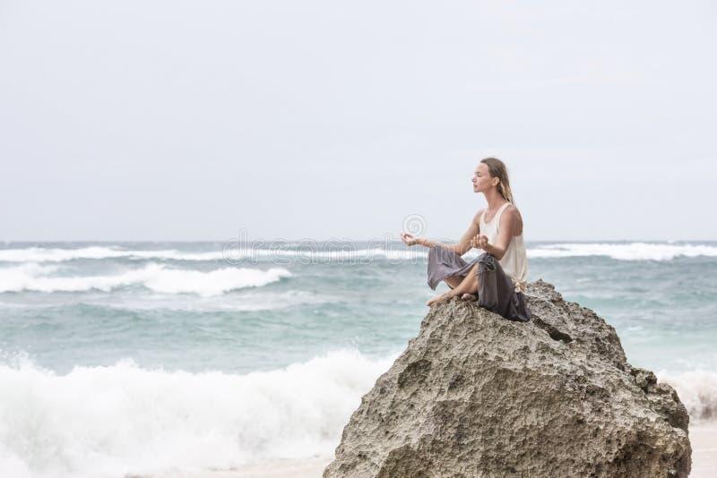Девушка сидит на взморье на утесе и размышлять в представлении женщины йоги стоковые фотографии rf