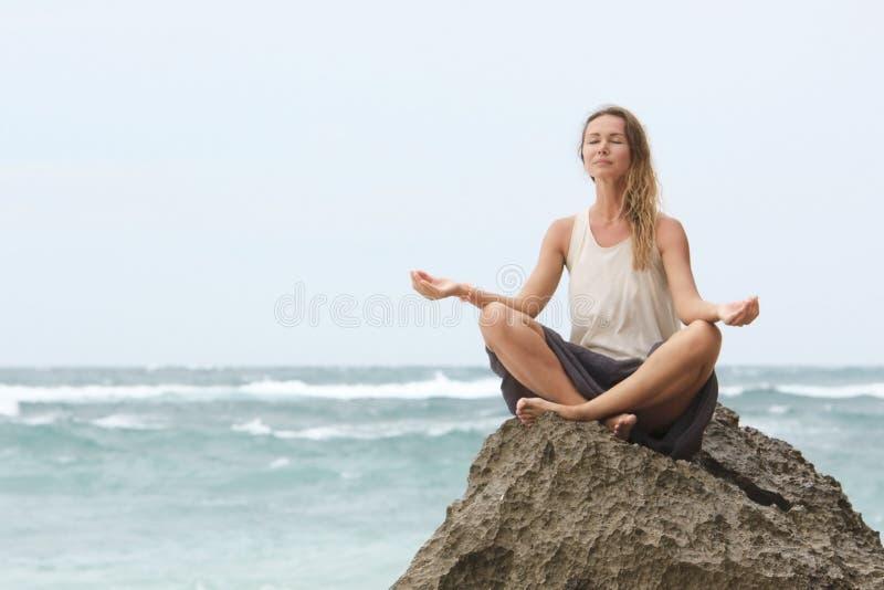 Девушка сидит на взморье на утесе и размышлять в представлении женщины йоги стоковые изображения rf