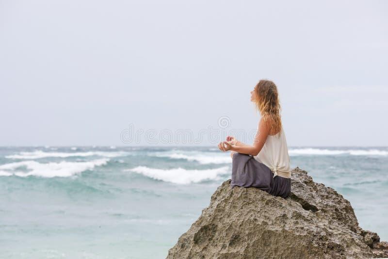 Девушка сидит на взморье на утесе и размышлять в представлении женщины йоги стоковое фото rf