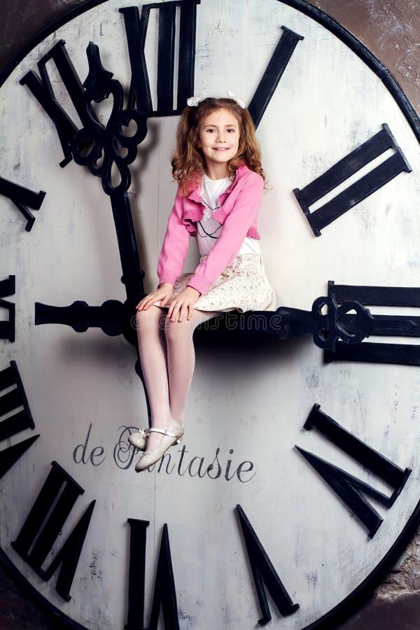 Девушка сидит на огромное по часовой стрелке стоковое фото rf