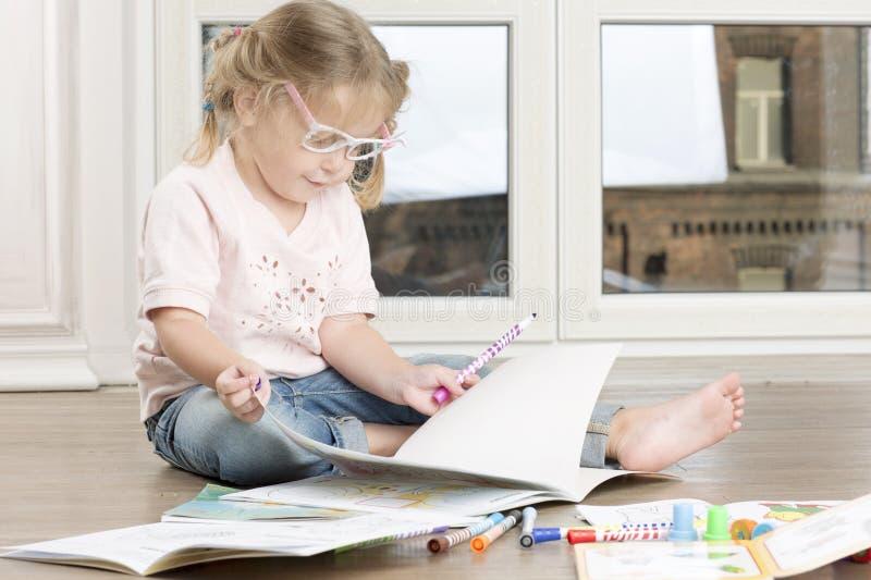Девушка сидит на поле и рисовать стоковое изображение rf