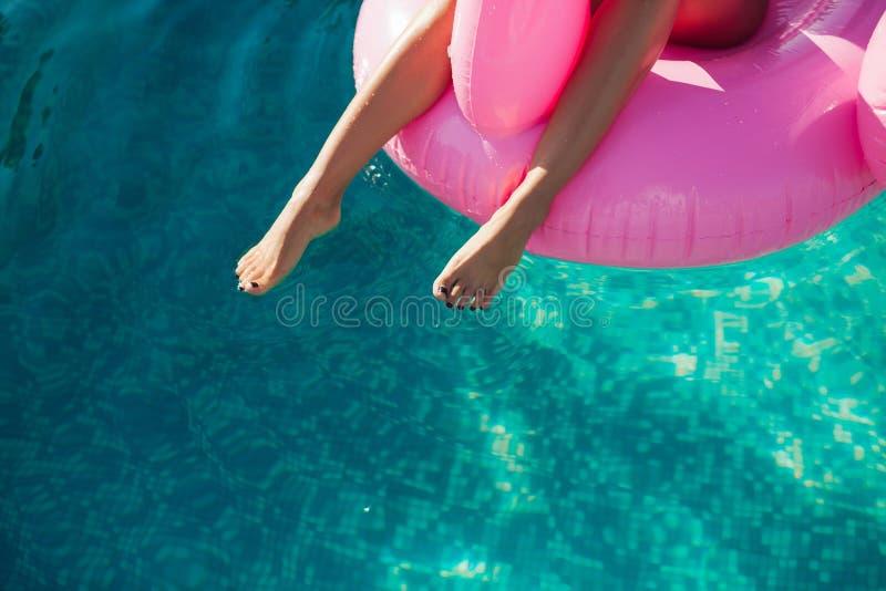 Девушка сидит на раздувных фламинго тюфяка в бассейне стоковая фотография rf