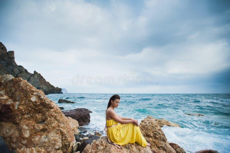 Девушка сидит на утесе на пляже против неба и моря стоковая фотография