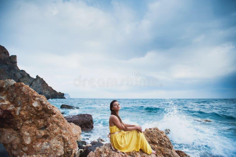 Девушка сидит на утесе на пляже против неба и моря стоковые изображения