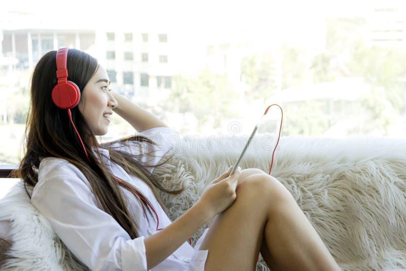 Девушка сидит ослабляет на ее софе слушает к музыке на наушниках стоковое фото rf