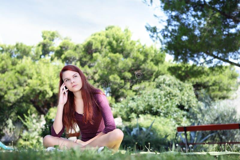 Девушка сидя в парке с сотовым телефоном смотрит вверх стоковое изображение