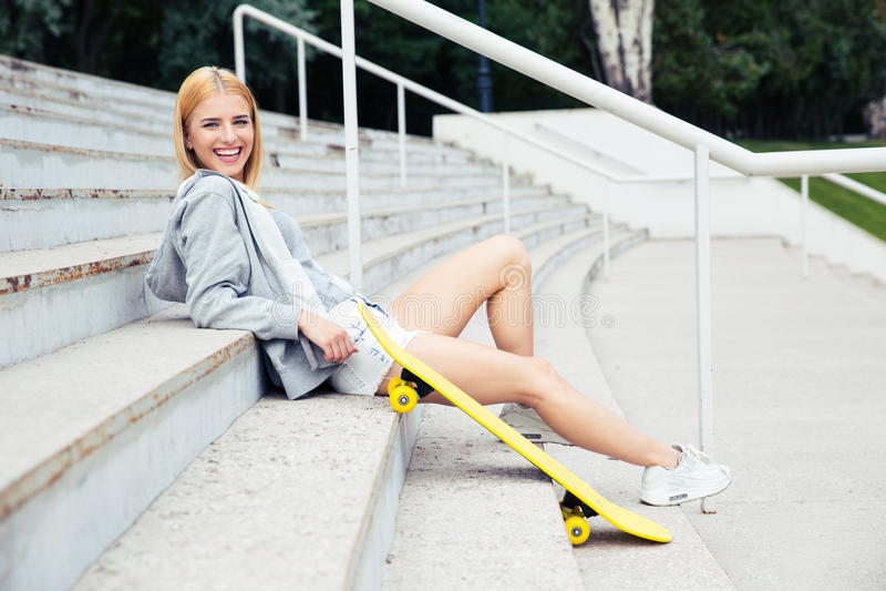 Девушка сидя на лестницах с скейтбордом стоковые изображения
