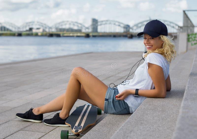 Девушка сидя на лестницах с longboard стоковая фотография