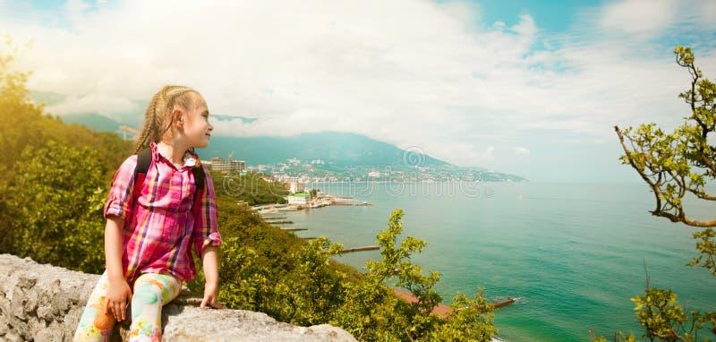 Девушка сидя на крае скалы смотрит в расстояние стоковое изображение rf