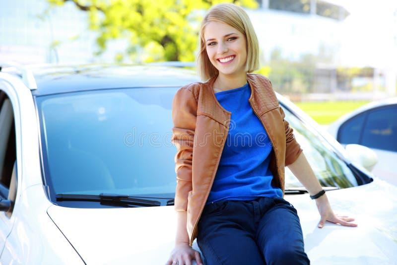 Девушка сидя на клобуке автомобиля стоковые фотографии rf