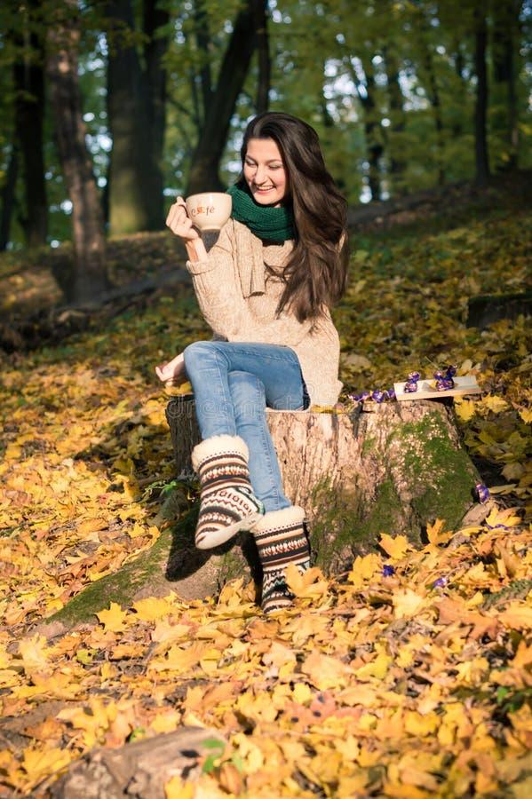 Девушка сидя на пне дерева стоковые изображения