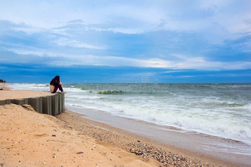 Девушка сидя на пристани смотря afar моря стоковое изображение rf