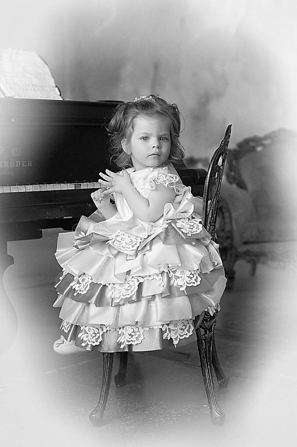 Девушка сидя на рояле стоковое фото rf