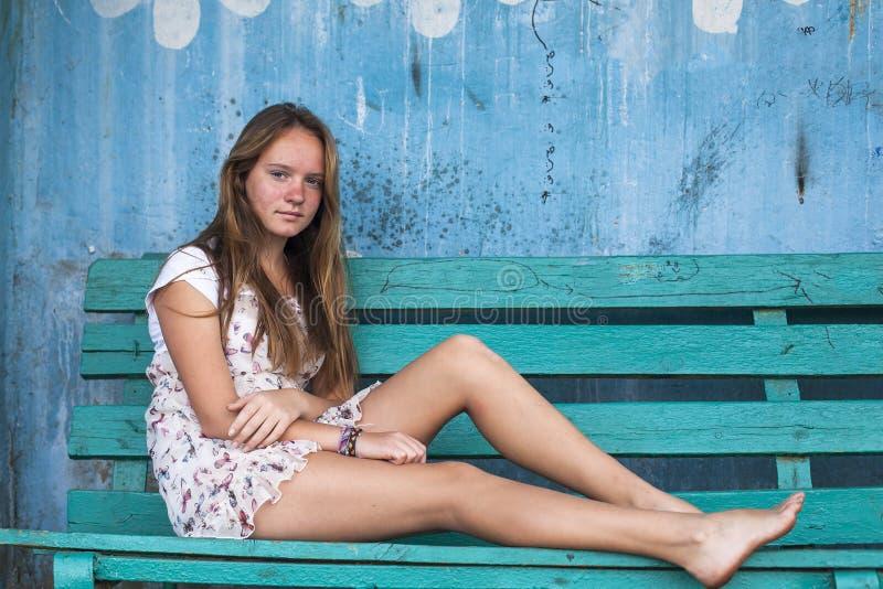 Девушка сидя на стенде, старая пакостная стена на предпосылке стоковое изображение