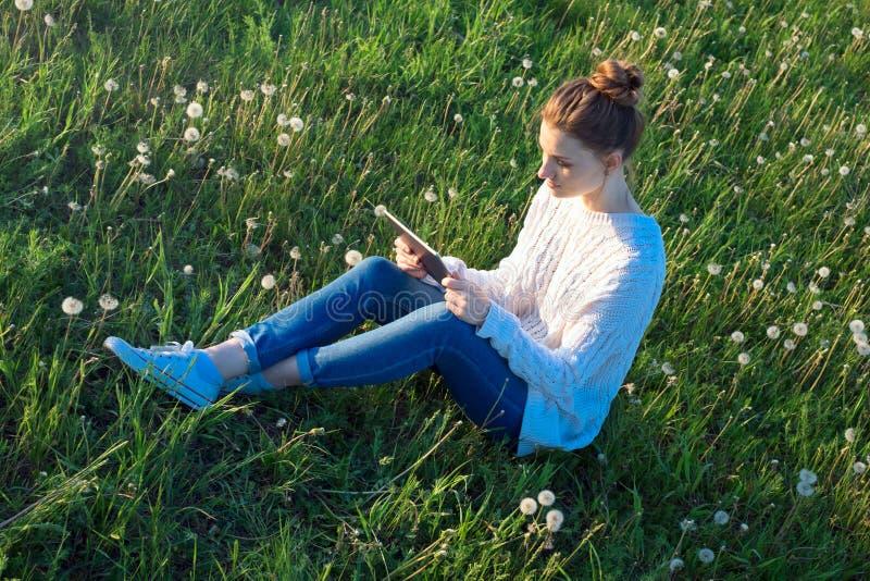 Девушка сидя на траве и смотря планшет стоковые изображения