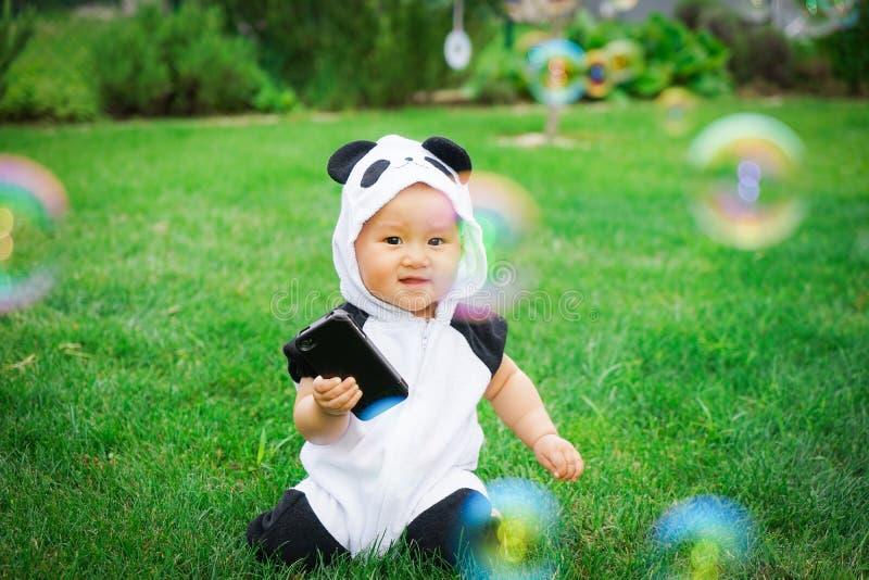Девушка сидя на траве с пузырями мыла стоковые фото