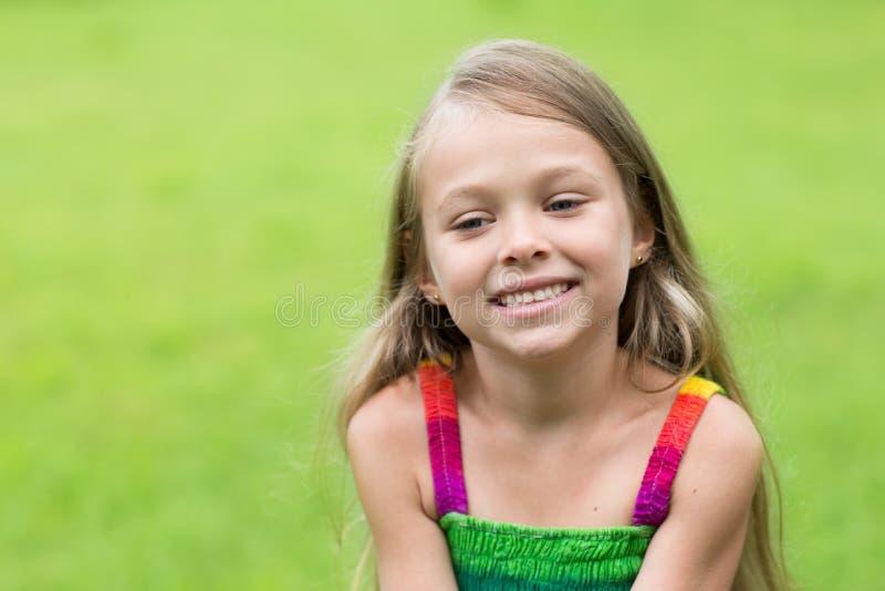 Девушка сидя на лужайке стоковые изображения