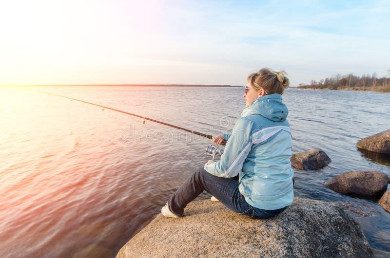 Девушка сидя на утесе с рыболовной удочкой стоковая фотография