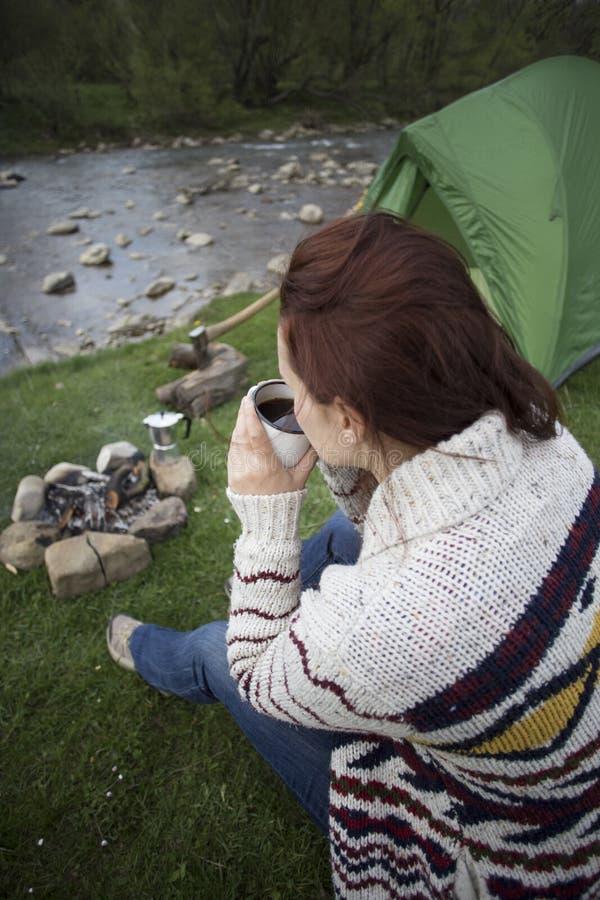Девушка сидя около лагерного костера на месте для лагеря смотря карту и выпивая кофе стоковая фотография rf