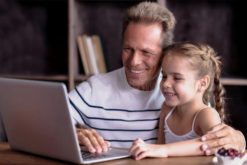 Девушка сидя перед компьтер-книжкой с ее дедом стоковая фотография