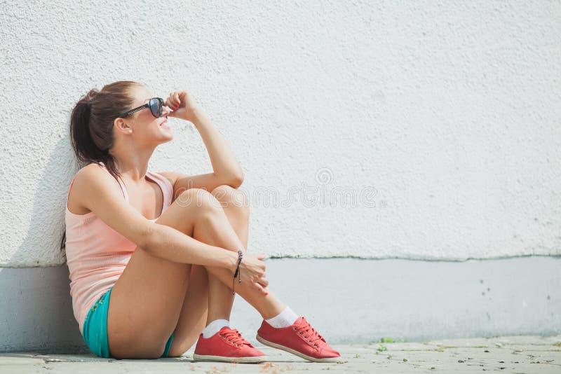 Девушка сидя самостоятельно в городской среде стоковые изображения